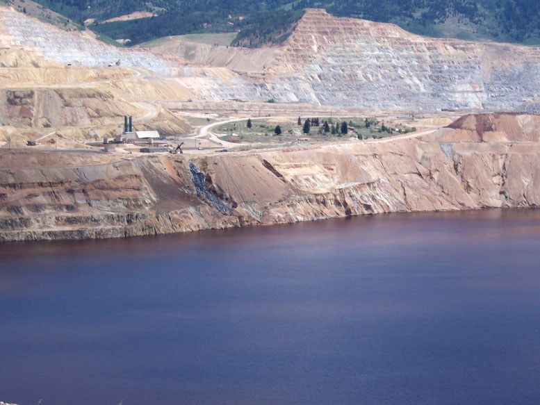 The northeast rim of the Berkeley Pit in July 2013, after a Feb. 2013 slough from the Pit wall knocked out a pump used for Montana Resources copper precipitation plant. When the precipitation operation was ongoing, Berkeley Pit water was pumped to a precipitation plant where copper was removed from the water. The water was then returned to the Pit, creating the waterfall seen in past years. Photo by Fritz Daily.