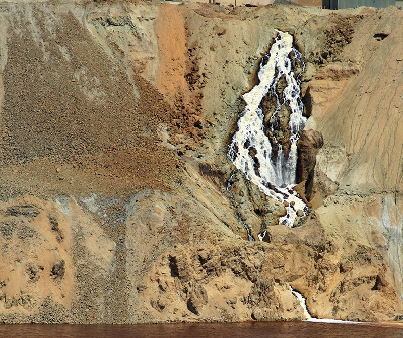 The waterfall on the northeast rim of the Berkeley Pit, near the Horseshoe Bend Water Treatment Plant as it appeared in 2009. The waterfall has stopped flowing since a Feb. 2013 slough from the Pit wall knocked out a pump used for Montana Resources copper precipitation plant. Photo by Justin Ringsak.