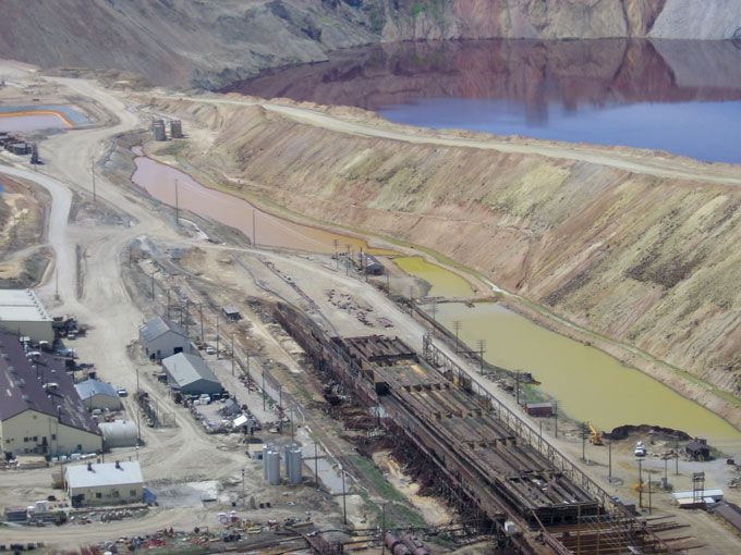 Montana Resources copper precipitation plant adjacent to the Berkeley Pit. A 2013 slough of material from the Pit wall into the water knocked out the 'precip' pump, and precip operations have since ceased. In precipitation, the copper-rich water is pumped over scrap iron, and, in a replacement reaction, the copper solidifies as sludge, while iron takes its place in the water. The water was returned to the Pit by gravity flow, thus not increasing or decreasing the total volume of Pit water. Photo by Justin Ringsak.